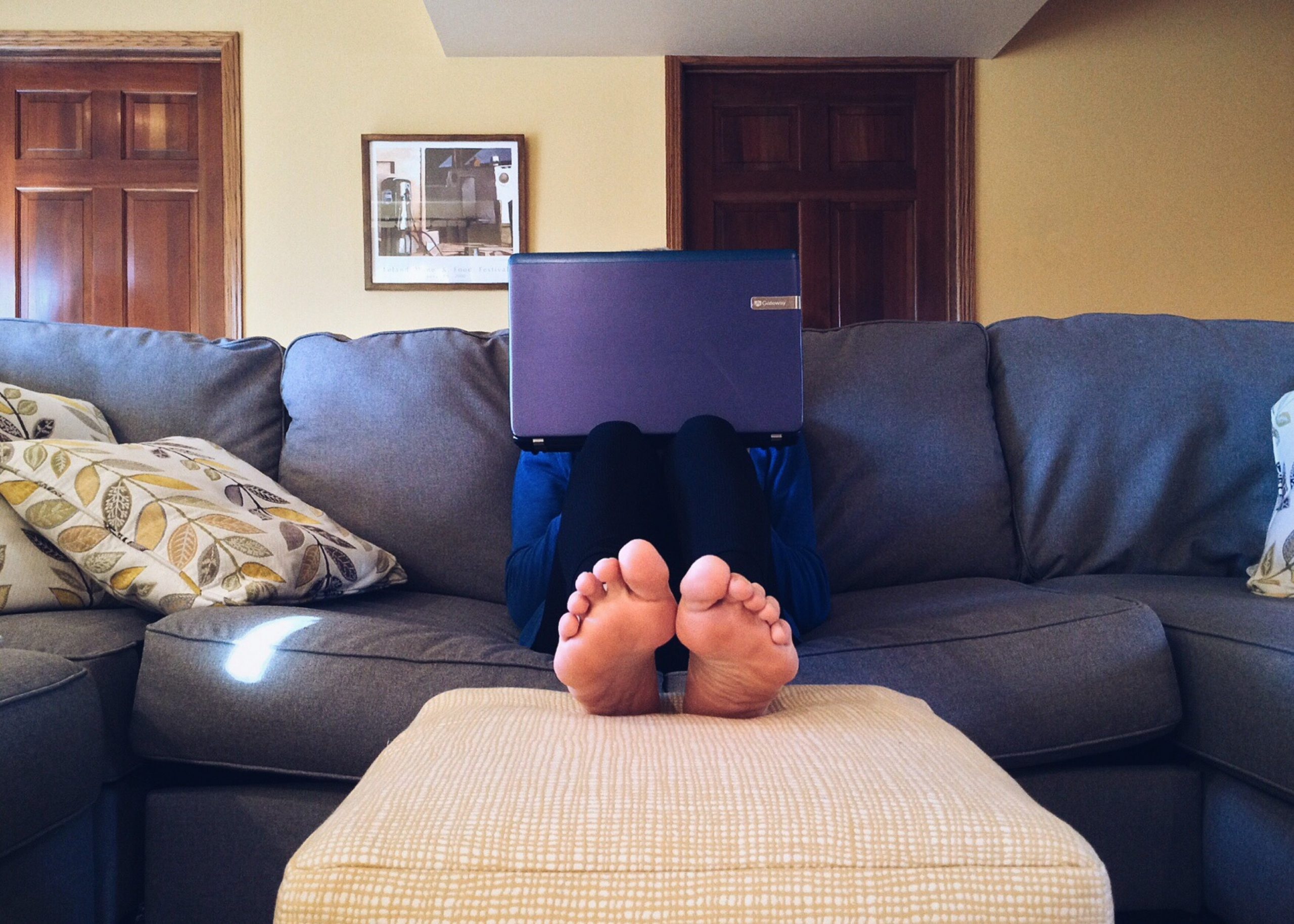 A barefoot person sits on a sofa with a laptop obscuring their face.